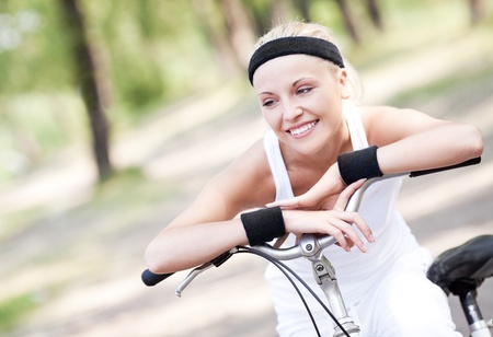 outsides: beautiful young blond woman  riding a bicycle on a warm summer day