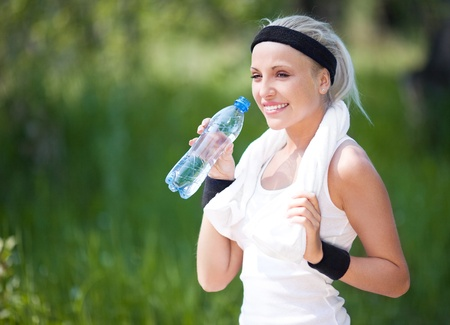 girl jogging: beautiful young blond sporty woman jogging in the park on a warm summer day and drinking water Stock Photo