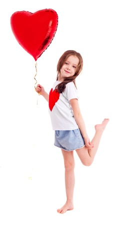 6 years: cute six year old girl wearing a T-shirt with a big red heart, isolated against white background