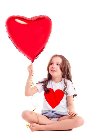 6 year old: cute six year old girl wearing a T-shirt with a big red heart, isolated against white background