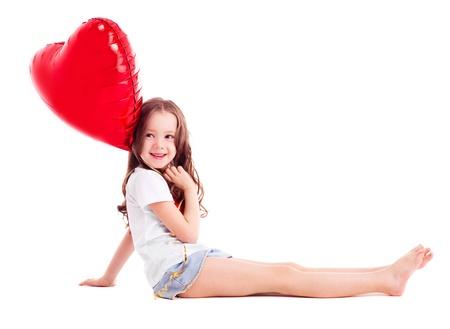piedi nudi di bambine: ragazza carina sei anni con un grande cuore rosso a forma di palloncino, isolato su sfondo bianco Archivio Fotografico