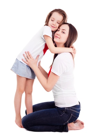 6 years: happy mother and her six year old daughter wearing T-shirts with big red hearts, isolated against white background