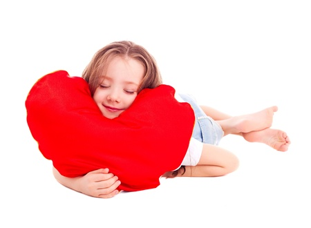 cute sleeping six year old girl  with a red heart-shaped pillow, isolated against white background photo