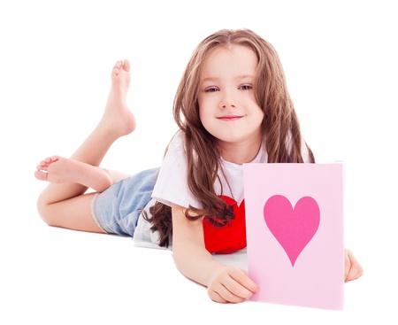 piedi nudi di bambine: ragazza carina sei anni con la carta di San Valentino tra le mani, isolato su sfondo bianco
