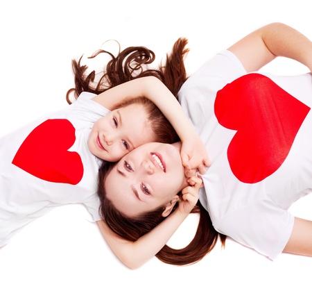madre e hija: feliz madre y su hija de seis años de edad, vistiendo camisetas con grandes corazones rojos, aislados sobre fondo blanco, vista superior