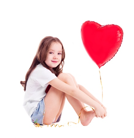 cute six year old girl  with a big red heart-shaped balloon, isolated against white background photo