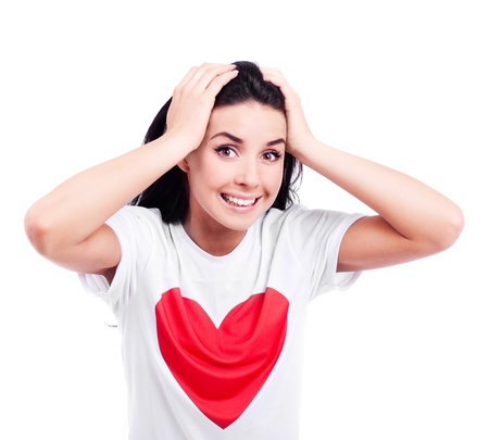 excited young  woman wearing a T-shirt with a big red heart, isolated against white background