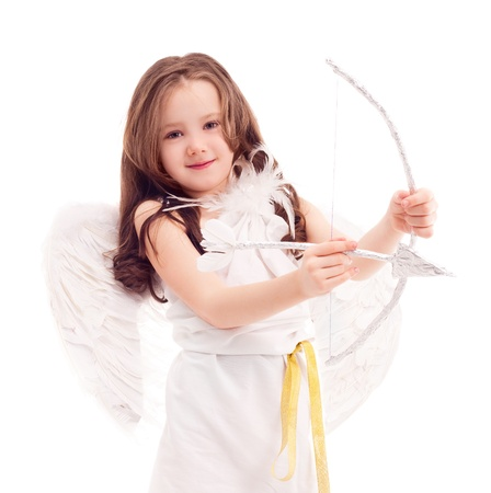 6 years: cute  six year old girl  dressed as a cupid with white wings, a bow and an arrow, isolated against white background