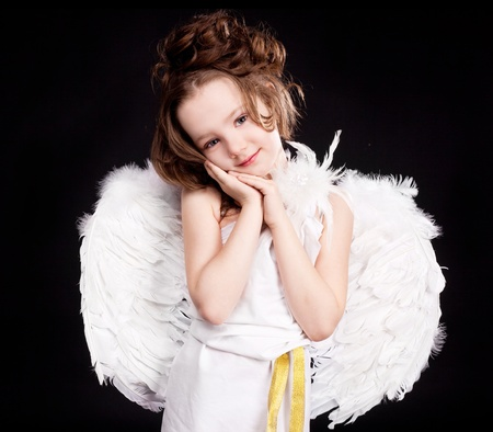 6 year old: cute  six year old girl  dressed as a cupid with white wings, isolated against black studio background Stock Photo