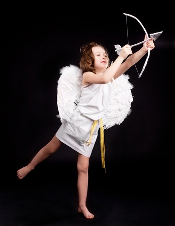 cute  six year old girl  dressed as a cupid with white wings, bow and arrow, isolated against black studio background Stock Photo - 12007917