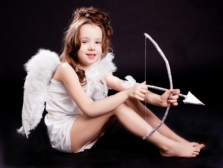 cute  six year old girl  dressed as a cupid with white wings, bow and arrow, isolated against black studio background photo