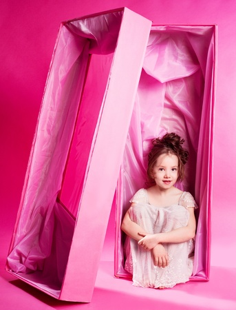 toy box: cute six year old girl as an alive doll in the pink box,  against pink studio background