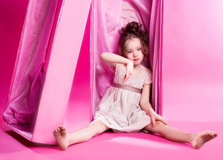 6 year old: cute six year old girl as an alive doll in the pink box, against pink studio background