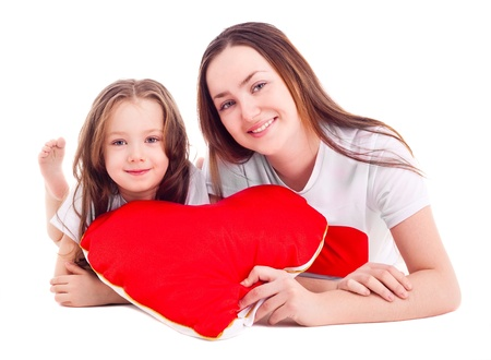 heartshaped: happy mother and her six year old daughter with a heart-shaped pillow, isolated against white background Stock Photo