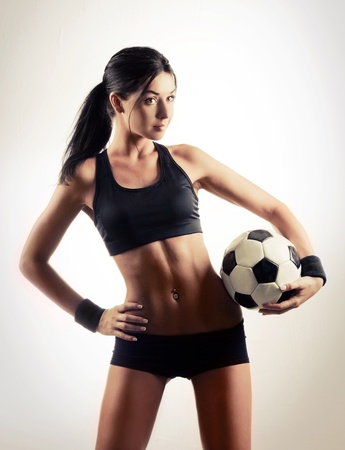 petite girl: high contrast studio portrait of a young beautiful sporty woman holding a football ball