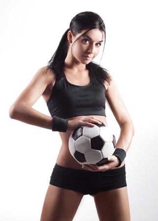 high contrast studio portrait of a young beautiful sporty woman holding a football ball  photo