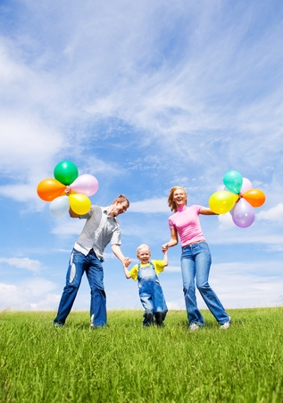 family celebration: happy family with balloons running outdoor on a warm summer day