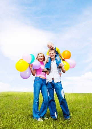 happy family with balloons  outdoor on a warm summer day Stock Photo - 12070744