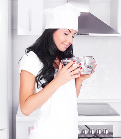 beautiful brunette woman cooking soup in the pot in the kitchen at home photo
