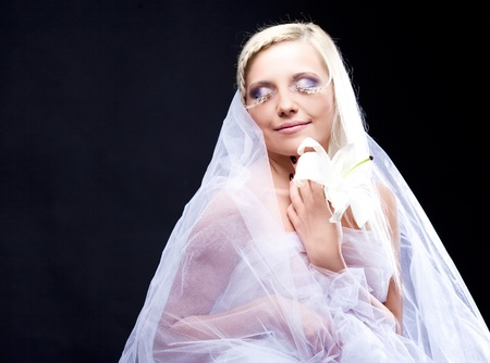beautiful young blond bride with a lily and creative makeup photo