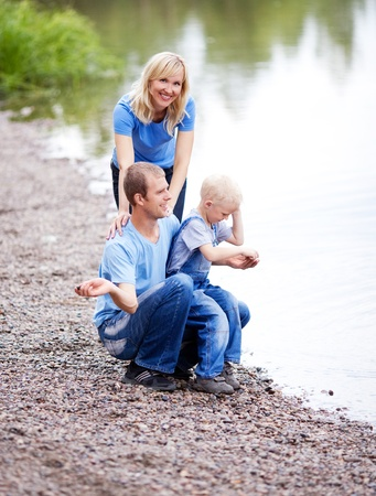 river stones: happy family  having a walk near the lake and throwing stones into the water outdoor on a summer day Stock Photo