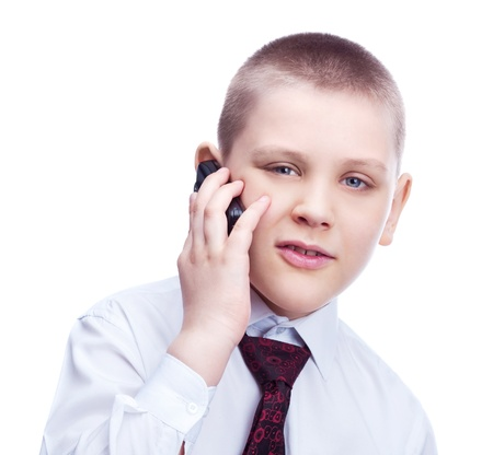 ten year old blond boy wearing a shirt and a tie, talking on the phone, isolated against white photo