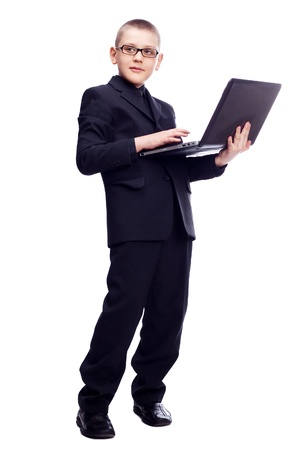 ten year old blond boy wearing a costume with a laptop, isolated against white background photo