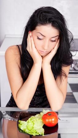 disorders: trastornado joven mujer mantiene una dieta y el consumo de verduras en la cocina en el hogar Foto de archivo