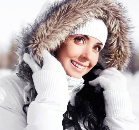 outsides: pretty young brunette woman wearing warm winter clothes outdoor