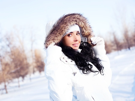 fur hood: pretty young brunette woman wearing warm winter clothes outdoor