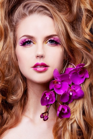 pink lips: studio portrait of a beautiful young modeln with luxurious long curly hair and an orchid Stock Photo