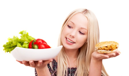 thoughtful young woman holding a hamburger with chicken and plate with vegetables, isolated against white background photo