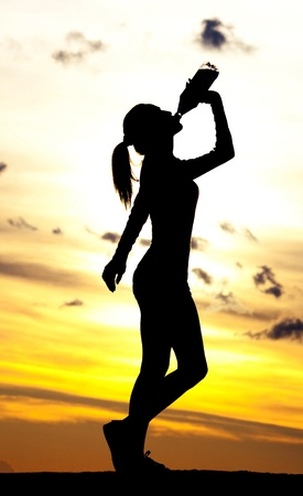 Silhouette of a  woman drinking water on the hill against yellow sky with clouds  photo