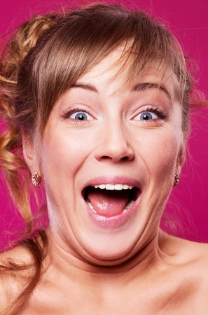 humorous portrait of an excited screaming young woman, isolated against purple studio background photo