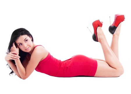 lying on the floor: beautiful  brunette woman wearing a red dress, isolated against white background