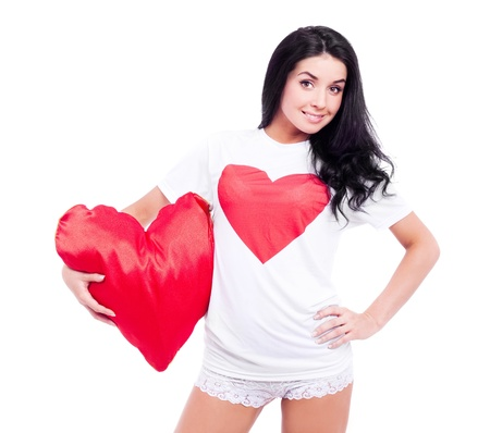 smiling young  woman wearing a  shirt with a big red heart and holding a heart-shaped pillow, isolated against white background Stock Photo - 12282650