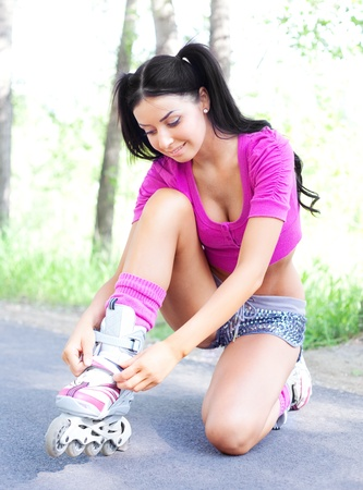happy young brunette woman fastening the roller skates and is getting ready to ride  in the park photo