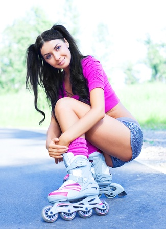 happy young brunette woman  roller skating in the summer park Stock Photo - 12282692