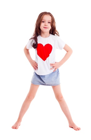 6 year old: happy smiling six year old girl wearing a  shirt with a big red heart, isolated against white background