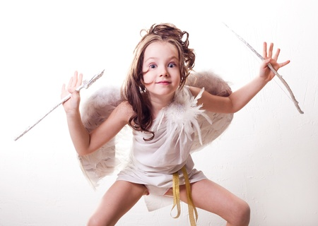 humorous portrait of a cute  six year old girl  dressed as a cupid with white wings, bow and arrow, against studio background photo