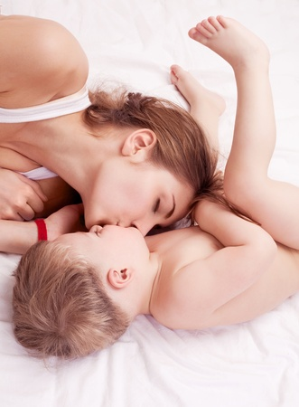 two year old: happy young mother and her two year old son embracing and kissing  in bed at home