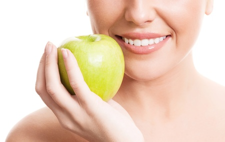 closeup of the face, hands and healthy white teeth of a woman holding an apple, isolated against white background  photo