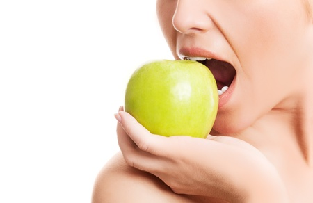 closeup of the face of a woman biting a green apple, isolated against white background  photo