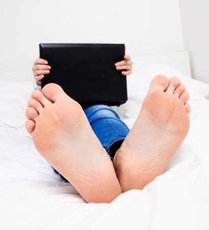 humorvolle Porträt einer Studentin mit dem Laptop im Bett zu Hause, an den Füßen konzentrieren Standard-Bild