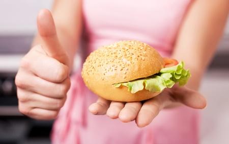 여자는 샐러드와 토마토 샌드위치를 들고와 그녀의 엄지 손가락을 게재하는 손