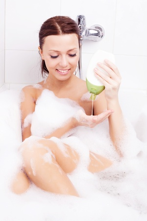 beautiful young brunette woman taking a relaxing bath with foam and using shampoo into her palm photo