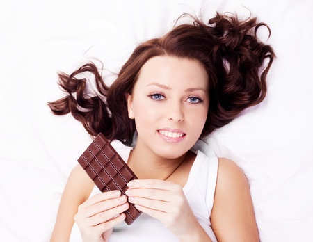 beautiful young  woman eating chocolate in bed at home photo
