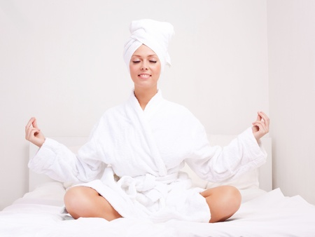 beautiful young woman wearing a towel and a white bathrobe meditating in  the bed at home photo