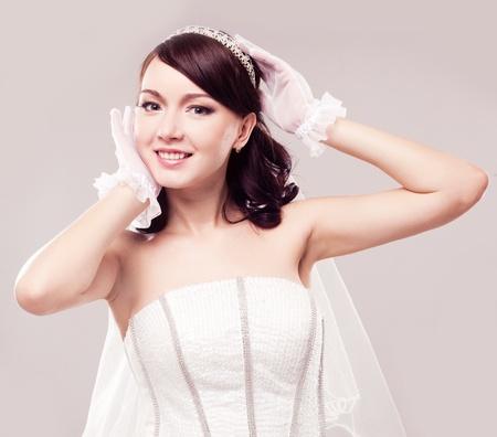 beautiful happy bride, isolated against grey studio background photo