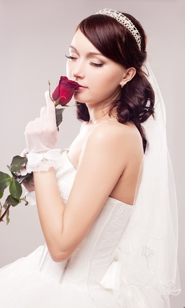 beautiful young bride with a rose, isolated against grey studio background photo